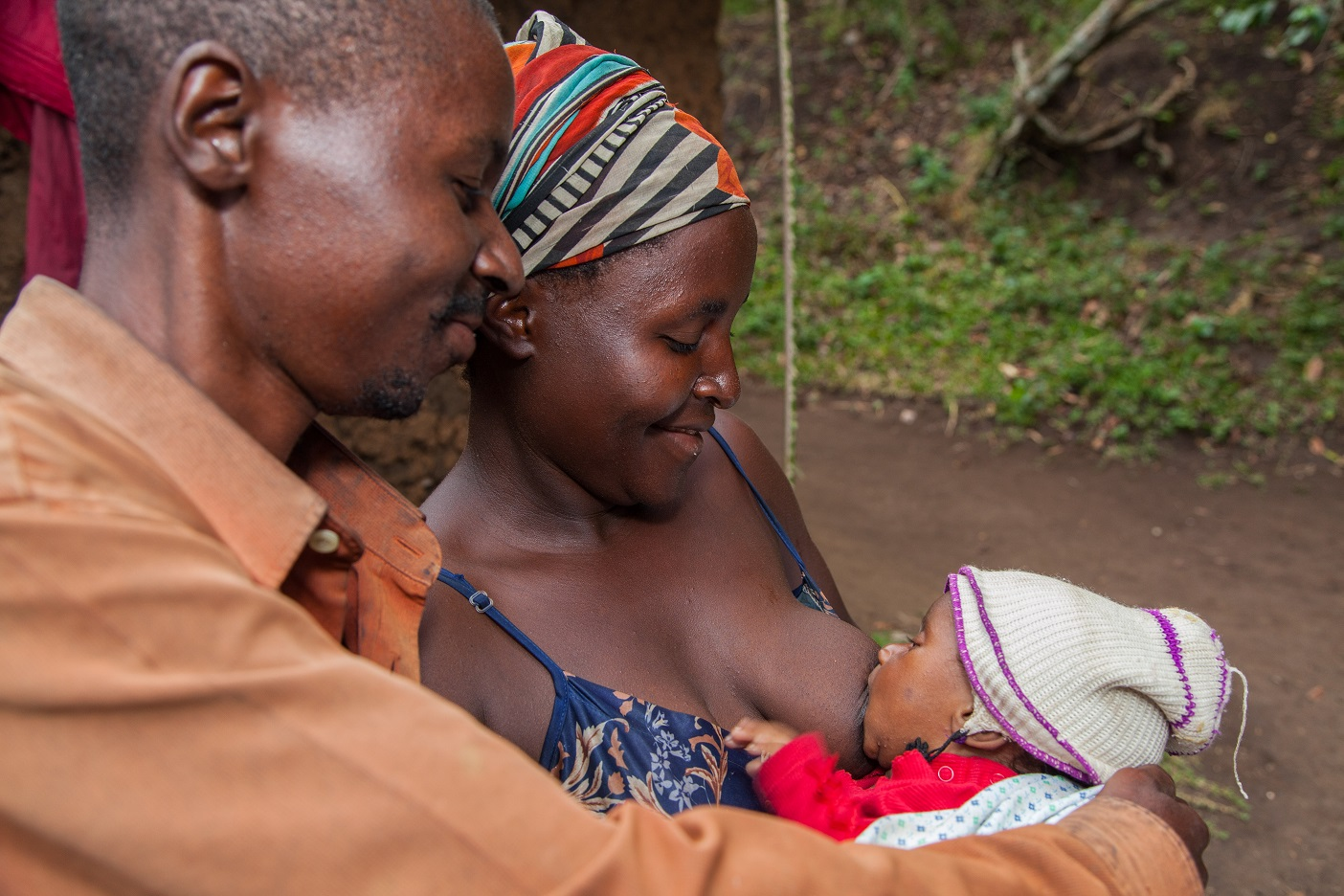 A husband supports his wife to breastfeed their baby